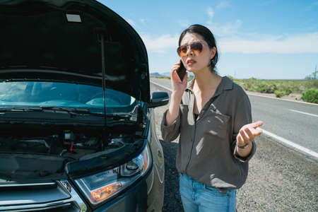 unhappy woman got something wrong with car and is calling for help. asian female traveler standing beside vehicle with open hood is describing her problems to insurance company via mobile. Zdjęcie Seryjne