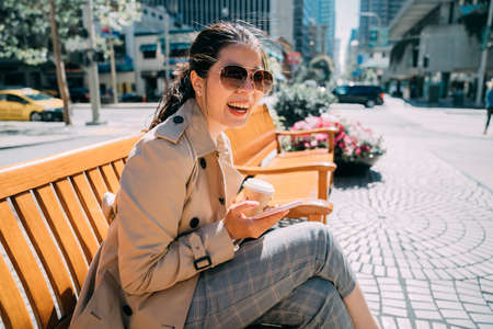 Young beautiful asian korean girl sitting on wooden bench holding paper cup of coffee and cellphone. confident positive woman in fashion sunglasses cheerful laughing and using mobile phone outdoor