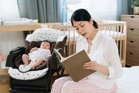 asian new mom sitting by her young kid is reading a story picture book to her newborn baby. nurturing and cultivating concept.