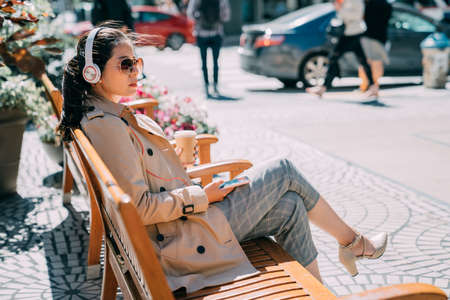 confident asian chinese woman in sunglasses listening to music from smartphone with headphones in city street. young girl with headset enjoy sunshine sitting on wood bench holding mobile phone.
