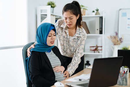 muslim pregnant woman is experiencing labor in office. painful young maternity girl worker is giving birth unborn baby. worried chinese woman colleague careful touching future mom belly in workplace