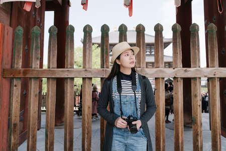 korean woman carrying camera standing back on wooden fence is looking away.