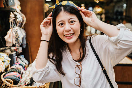 young lovely lady face camera smiling while trying on cute headband in accessories store. beautiful asian chinese female shopping in shop vendor. charming woman laughing cheerful looking lens.