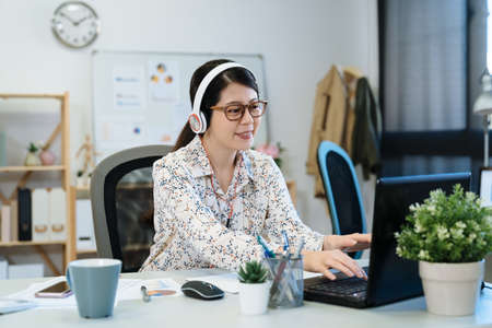 Young pretty asian japanese woman in eyeglasses is working in modern office. relax female employee in headphones listening to music and smiling in studio. lady worker typing on laptop computer. Zdjęcie Seryjne