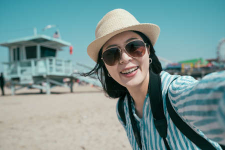 Beautiful young asian korean woman taking selfie on sandy beach by lifeguard tower. charming girl in sunglasses and straw hat face camera and smiling. female traveler enjoy sunshine under blue sky. Zdjęcie Seryjne