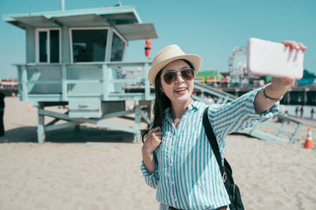 happy young female travel backpacker hold cellphone taking selfie with open lifeguard station. sunny day beach in Santa Monica los angeles USA. smiling girl tourist making self photo on mobile phone Zdjęcie Seryjne