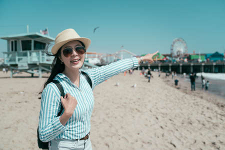 pretty young asian chinese woman standing and point finger at amusement park. cheerful beautiful girl traveler relax on beach relax on holidays. happy female standing by lifeguard stand on sunny day