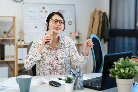 Joyful young asian japanese woman employee wearing headset with cellphone as microphone sitting at desk at modern office. confident girl staff in glasses and earphones enjoy music singing in studio Zdjęcie Seryjne