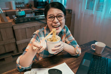 young asian japanese woman laughing eating noodles with chopsticks in dining room while doing deadline work in late night. lady enjoy unhealthy fast food ramen soup in home kitchen face camera smile