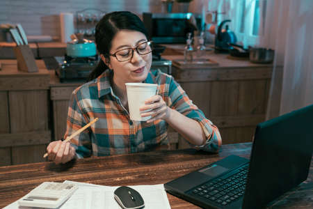 Asian korean businesswoman eating instant noodles at kitchen for bedtime snack time. charming female enjoy ramen soup in paper cup smiling. happy lady with unhealthy food and laptop working in night