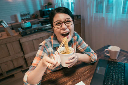 smiling asian chinese woman eating fast food with chopsticks at dining table in home dark kitchen. happy girl face camera cheerful laughing while having delicious instant noodles in disposable cup