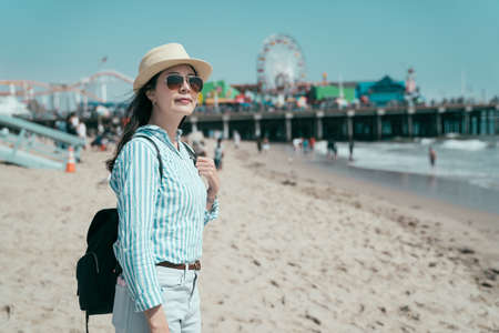 side happy smiling young girl traveler in straw hat and sunglasses carrying backpack. elegant female tourist standing sandy beach enjoy beautiful ocean view. bokeh of amusement park under blue sky.