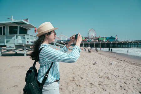 Travel lifestyle concept. side view beautiful asian chinese female tourist in straw hat and sunglasses taking photo on mobile phone while stand on sandy beach. girl traveler photographing cellphone