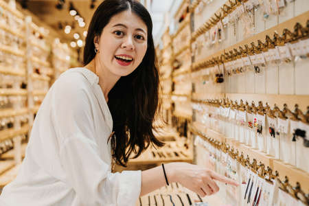 hipster asian chinese woman looking for fancy jewelry and accessories in market shop. charming lady joyful point finger at beautiful earrings on shelf and face camera smiling showing to boyfriend.