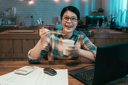 hungry businesswoman in glasses eating instant noodles fast food in disposable cup while working and using computer laptop and smiling face camera. happy young asian chinese girl holding ramen soup Zdjęcie Seryjne