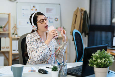 Young modern office manager woman singing favorite song with smartphone as microphone while listening to music in headphones at workplace. elegant businesswoman carefree relax in modern studio.