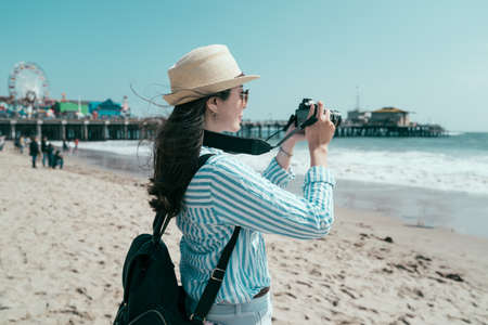 asian japanese woman backpacker having fun on beach with blue sea taking picture on camera. beautiful lady tourist wearing hat and sunglasses carrying backpack. female traveler enjoy ocean view.