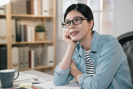 Portrait of beautiful teenage asian japanese girl smiling thinking while studying on table in bright home. happy college female student leaning and daydreaming future. confident woman in glasses Zdjęcie Seryjne