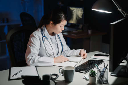 asian japanese female doctor sitting at table and writing on document report in hospital office at late night. Medical healthcare staff service concept. hard working woman nurse reading notebook Banque d'images