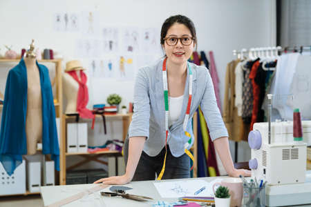 Successful fashion designer woman worker in studio. attractive young asian chinese female staff wear glasses putting hands on work desk and looking at camera with smile while standing in workshop.