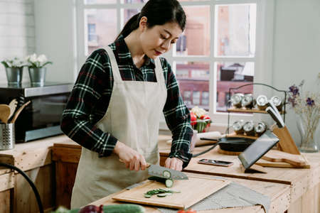 elegant asian chinese woman wearing apron cutting vegetables in modern kitchen with tablet on table. beautiful housewife prepare healthy meal with fresh cucumber into slices in cooking place indoor. Archivio Fotografico