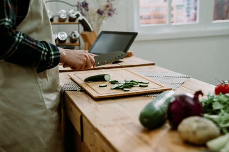 unrecognized asian chinese woman cutting fresh vegetables on chopping board with digital tablet on kitchen counter table at home. elegant lady hold sharp knife with cucumber slice in cooking place
