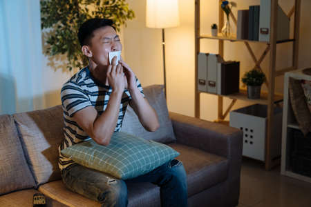 Handsome asian chinese man kiss winning lottery ticket and feeling excited. cheerful male watching tv program with number paper of gambling. young joyful guy celebrating in living room sofa at night