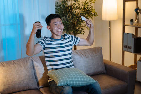 Portrait happy young japanese man with pumping fists ecstatic celebrates success in dark living room in apartment at night. cheerful guy sitting on couch hand hold remote control and lottery ticket