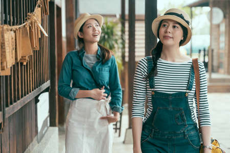 two happy girl tourists walking in corridor by japanese traditional wooden house. curious lady friends enjoy sightseeing in monument building. group female friend travel in Tokyo Japan in spring time