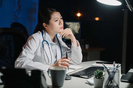 Serious thoughtful asian chinese woman doctor working with computer at table in dark workplace. pensive lady medical staff frowning and staring at pc screen thinking solution of patient problem. Zdjęcie Seryjne