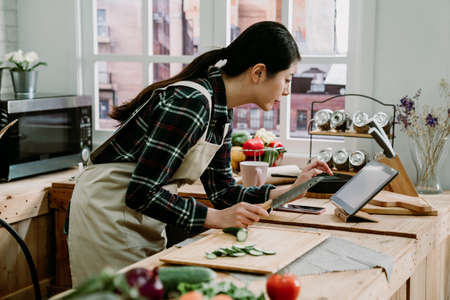 Happy young asian japanese woman cutting vegetables for healthy salad meal from online recipe and looking at digital tablet computer in modern kitchen. housewife searching cooking step on touch pad