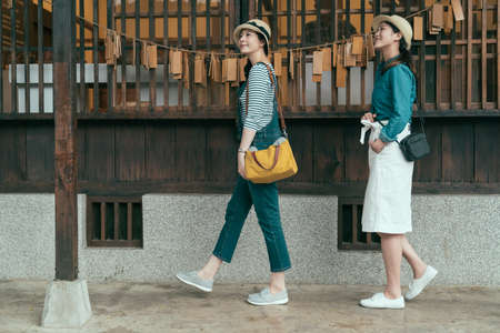 full length side view of two asian attractive girl travelers walk in line and looking side during sightseeing in temple. beautiful ladies enjoy sunny day visiting japanese traditional wooden house Zdjęcie Seryjne