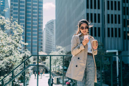 Young smiling businesswoman wear spring coat and sunglasses typing message on mobile phone and drinking coffee in city. modern skyscraper in background on sunshine. positive lady hold to go tea cup