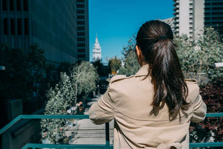 back view portrait of asian businesswoman wearing stylish spring coat leaning railing standing against balcony view of san francisco in business working area. tall building in back on sunny blue sky