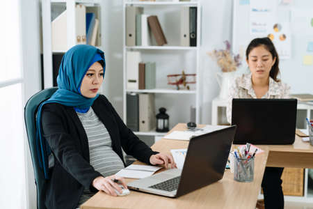 Young business people working together at office. muslim pregnant woman in headscarf sitting at workplace typing on laptop computer with colleagues concentrated using notebook pc in background.
