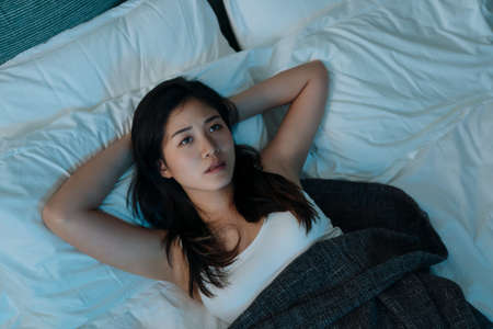 young beautiful asian korean woman at home bedroom lying in bed late at night trying to sleep suffer insomnia sleeping disorder. girl scared on nightmares look sad worried in mental health concept