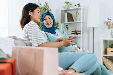 Excited asian korean lady with pregnant muslim sister sitting on couch in home living room. joyful islam woman and friend relaxing in sofa with shopping bags browsing online sale website on cellphone