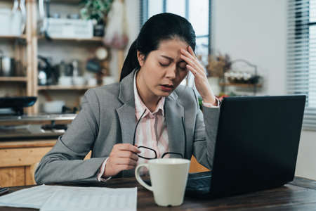 tired asian businesswoman feeling dizzy from overworking is rubbing her temple. frowning korean woman looking fatigued has sore eyes so takes off glasses for a rest.