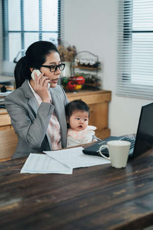 chinese businesswoman with toddler is changing ideas with partner through mobile and looking charts on computer. female manager and holding infant is checking online order with customer on phone. Archivio Fotografico