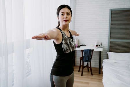 portrait of chinese girl practicing yoga warrior two with a smile. asian young lady standing with arms extend evenly in opposite directions, palms facing down  and gazing at a certain point.