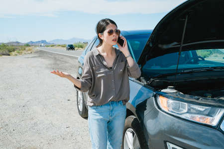 chinese woman speaking on mobile by car open hood is feeling dissatisfied. discontented female driver is complaining on phone about waiting long hours for towing company to come. Archivio Fotografico