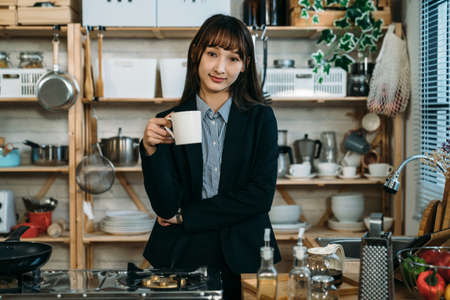 Pretty business woman having breakfast and drinking juice in the kitchen. Welcome a wonderful day for the new challenge work. Archivio Fotografico