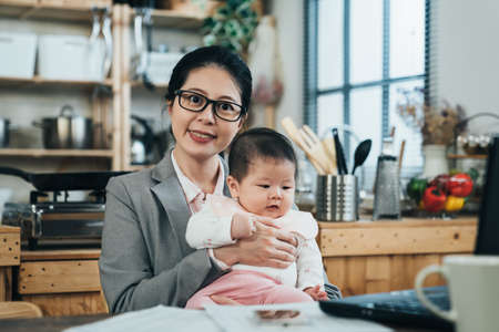 loving asian mother cuddling her adorable child is smiling happily. chinese lady wearing formal suit is holding her cute baby with a pleasant look. Archivio Fotografico