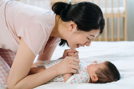 korean new mother with smile leaning toward her baby daughter and holding her hands gently. portrait of mom having strong bonding with baby.mother's day concept