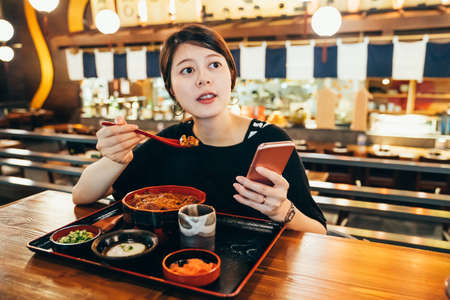Asian chinese young woman enjoy japanese food rice with eel grilled and scallop in bowl in fish market tokyo japan. female tourist sitting in local traditional izakaya trying unadon using cellphone Archivio Fotografico