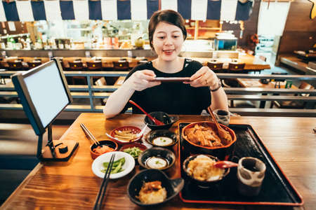 happy hungry girl traveler travel in tokyo japan and taking photo of japanese meal set on wooden table by mobile phone. beautiful lady smiling photographing on cellphone with unadon and side dishes