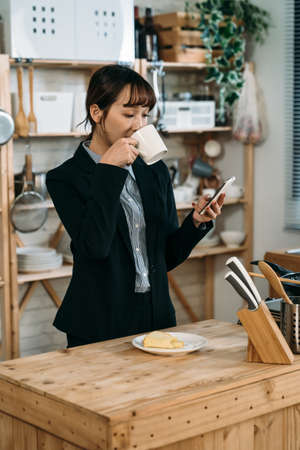 A saleswoman use her new cell phone to reply the request on line and has a breakfast with bread and coffee before working time. Archivio Fotografico