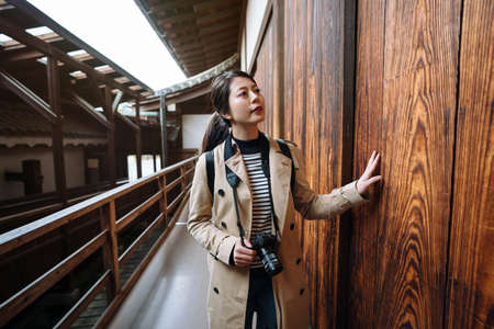 asian female traveler touching wooden wall is immersed in the feeling of nostalgia. chinese woman visitor standing in corridor with hand on wall is thinking about the history of the ancient building.