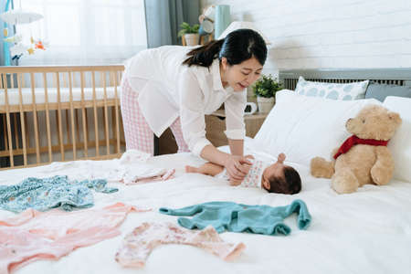 asian millennial woman interacting with her daughter before changing clothes for her. pleasant ambience japanese mom playing with her baby lying on bed scatter with baby clothes Archivio Fotografico