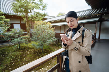 pleasant asian woman standing by japanese style garden is browsing her phone. smiling korean female traveler in Japan is sending pictures of the garden's landscape design to friends with cell phone.